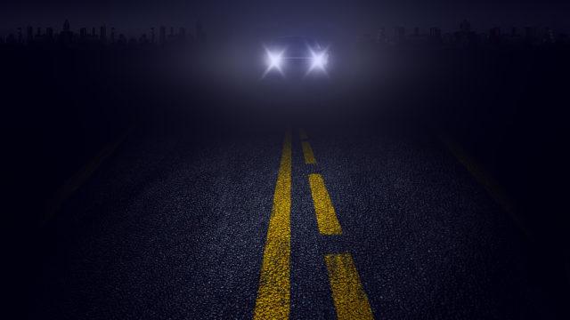 A car drives at night on a dark road